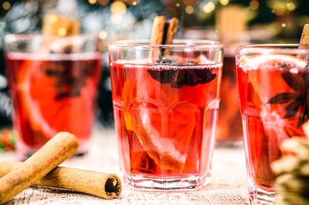 Глинтвейн красное вино со специями и рождественскими фруктами на деревенском деревянном столе с рождественскими цветами и огнями.