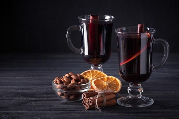 Mulled wine banner. glasses with hot red wine and spices on dark background.