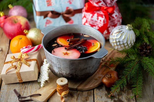 Mulled wine in a beautiful glass next to the saucepan. hot drink in a glass. christmas concept. family evening with a hot drink.
