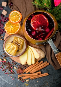 Mulled wine, blue pine tree branch and spices on wooden background.