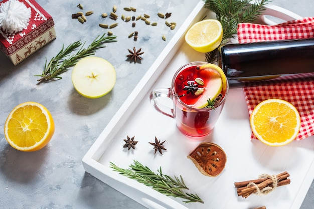 Mulled wine, a bottle of red wine, spruce branches, cinnamon, orange and lemon on white tray on concrete background.