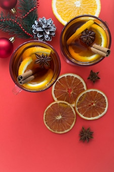 Mulled wine and christmas composition on the red background. top view. copy space. location vertical.