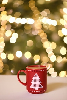 Mulled wine, christmas tea in a red mug with a christmas tree