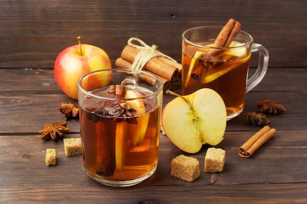 Глинтвейн из сидра в стеклянных кружках с корицей, анисом и яблоками.