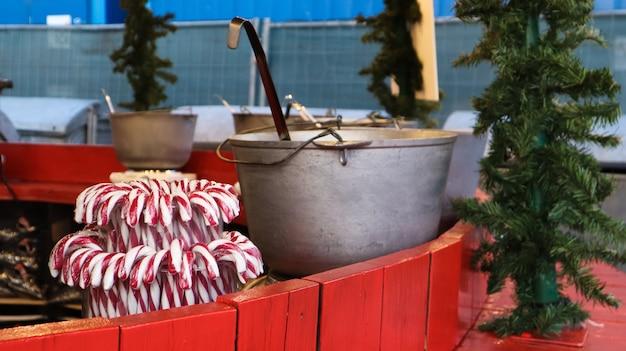 밖에서 화덕에 굽는 mulled wine. 겨울 음료의 비타민. 겨울에 크리스마스 시장에서 거리 식당입니다. 뜨거운 mulled 와인. 뜨거운 와인 가마솥 위에 짙은 증기.