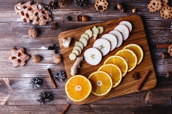 Mulled wine cooking. Oranges, apples and species lie on wooden table