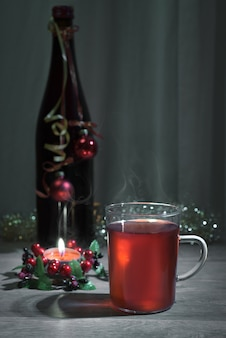 Mulled wine, decorated bottle and burning candle