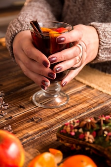 Mulled wine in female hands, spices and fruit ingredients,