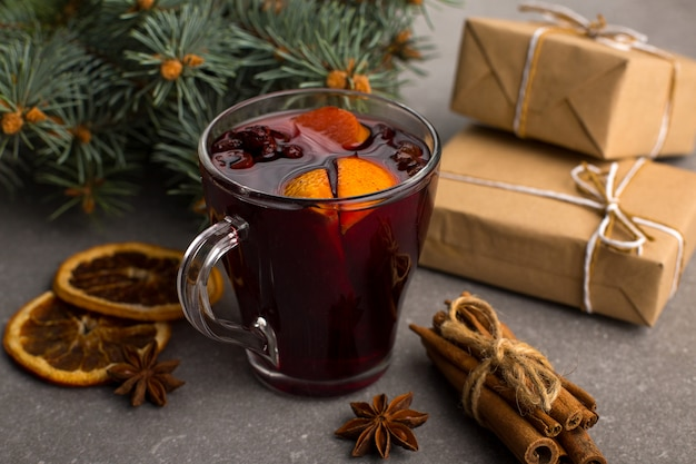 Mulled wine, a gift and spices on the table next to the tree