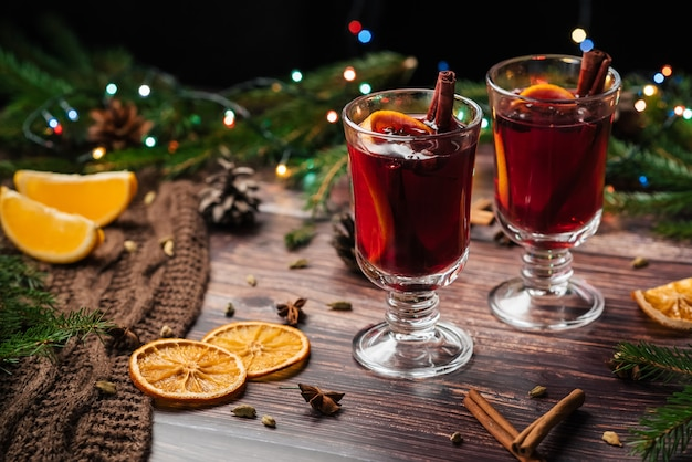 Mulled wine in glass glasses with orange slices, cinnamon sticks and spices