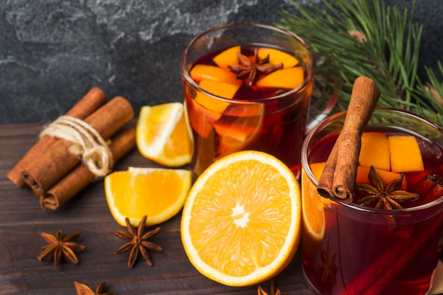 Mulled wine glasses with fir tree branches on wooden table