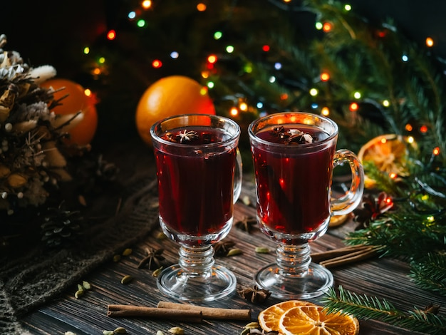 Mulled wine in glasses with orange slices and spices on a wooden table with a christmas garland. traditional alcoholic drink