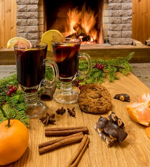 Mulled wine glintwine in drinking glasses and christmas decorations, against cozy fireplace.