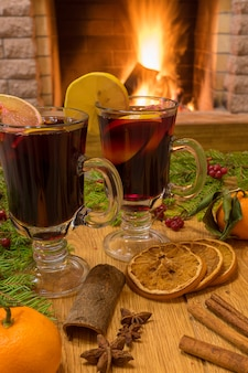 Mulled wine glintwine in glasses and christmas decorations, against cozy fireplace
