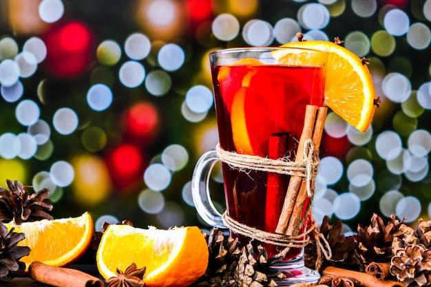 Глинтвейн горячий рождественский напиток со специями на темном фоне. дольки апельсина, палочки корицы, новогодние шишки, яркое боке. атмосфера праздника, деревенский стиль. идея создания поздравительных открыток