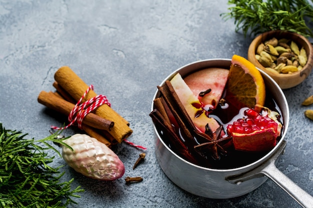 Mulled wine hot drink with citrus, apple, pomegranate and spices in aluminum casserole with vintage hristmas tree toys and fir branch on concrete surface.
