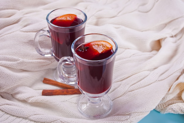 Mulled wine hot drink with citrus, apple and spices in a drink glasses.