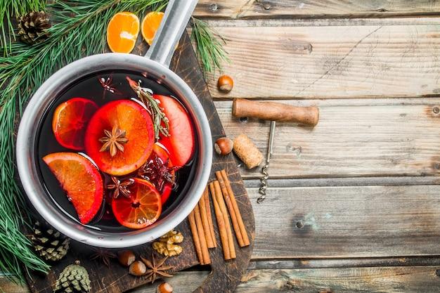 木製のテーブルの上のスパイスの鍋でホットワイン。