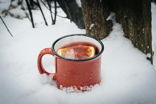 Глинтвейн в красной чашке. горячий зимний напиток на открытом воздухе в снежном зимнем лесу в холодную погоду.