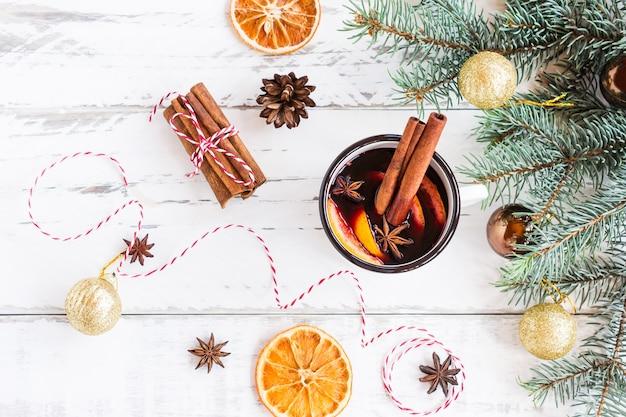 Глинтвейн в белой кружке. горячее пряное вино с корицей и звездчатым анисом. праздничная открытка на рождество.