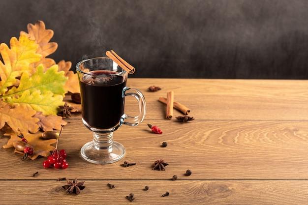 Глинтвейн в стеклянных чашках с корицей и анисом на деревянном столе. фон из опавших дубовых листьев.