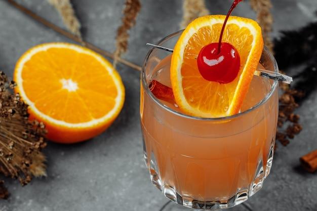 Глинтвейн в стеклянных бокалах с апельсиновыми яблоками и корицей. горячий рождественский напиток на сером столе