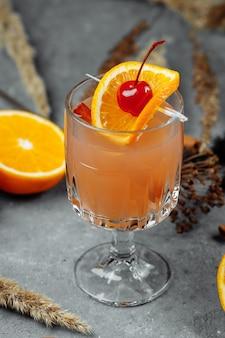 Глинтвейн в стеклянных бокалах с апельсиновыми яблоками и корицей.