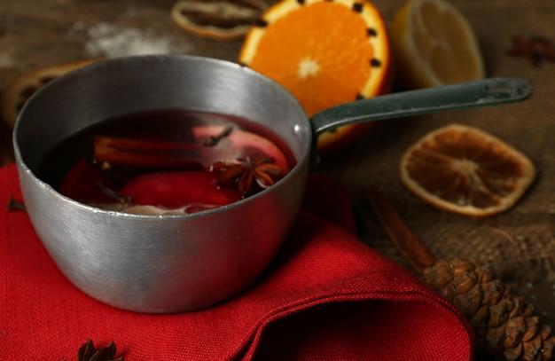 Глинтвейн в сотейнике на украшенном красной салфеткой, корице и апельсине деревянном столе