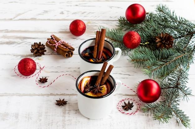 Глинтвейн в белых эмалированных кружках со специями и цитрусовыми на деревянном столе с еловыми ветками и рождественскими подарками.