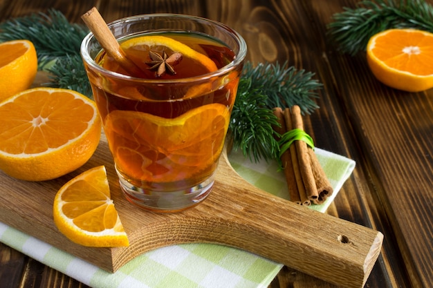 Mulled wine and mandarins on the wooden cutting board