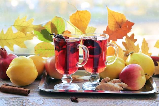 ホットワインの有機フルーツ秋は木製のテーブルにスパイスを残します家庭料理感謝祭