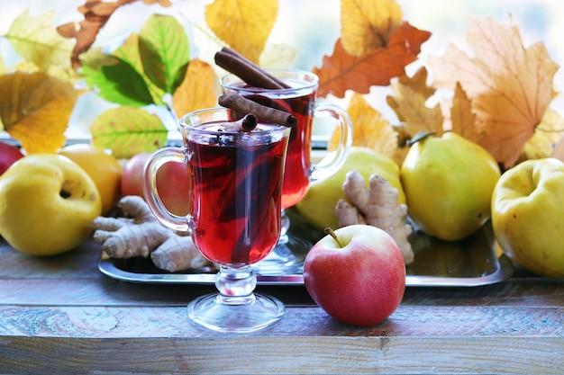 ホットワインのオーガニックフルーツ秋は木製のテーブルにスパイスを残します感謝祭