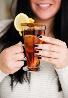 Mulled wine and punch are poured into a glass from a large saucepan.