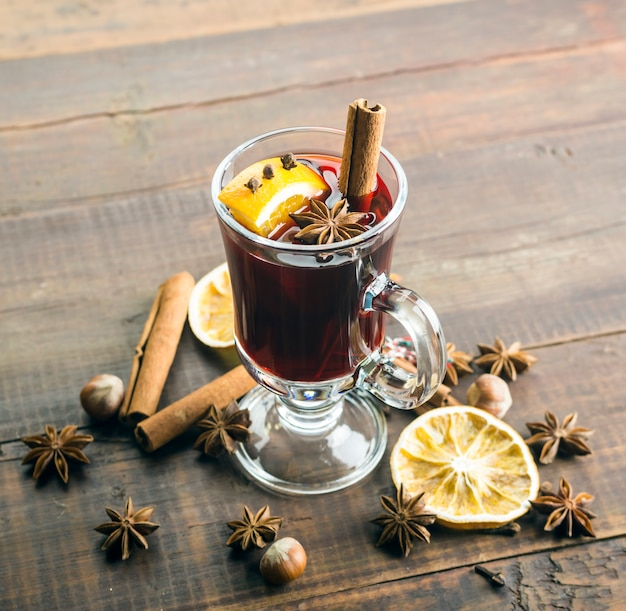 Mulled wine and spices on wooden .