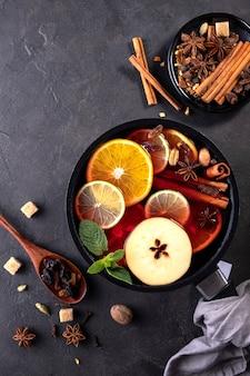 Глинтвейн традиционный рождественский горячий напиток с цитрусовыми, яблоками и специями в кастрюле. вид сверху на черном фоне. рецепт приготовления.