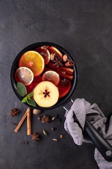 鍋に柑橘類、リンゴ、スパイスを入れたホットワインの伝統的なクリスマスの温かい飲み物。黒の背景に上面図。レシピ。