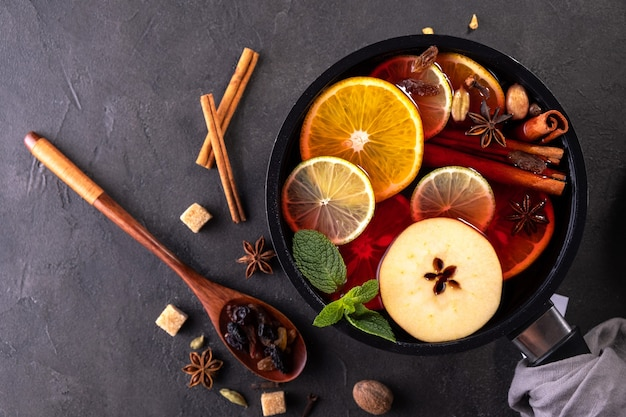Mulled wine traditional christmas hot drink with citrus, apple and spices in pan. top view on black background. recipe.