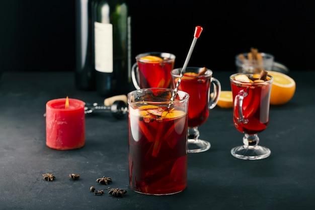 투명한 유리잔에 있는 멀드 와인 겨울 음료와 탁자 위의 주전자, 클로즈업