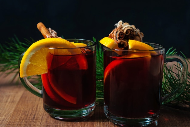 木製の背景に芳香のスパイスとオレンジの部分とホットワイン