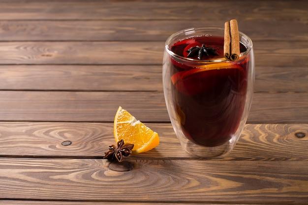 シナモン、スターアニス、オレンジ、ガラスガラス、木製の背景にホットワイン