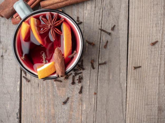 Mulled wine with cinnamon sticks and star anise on a wooden table.