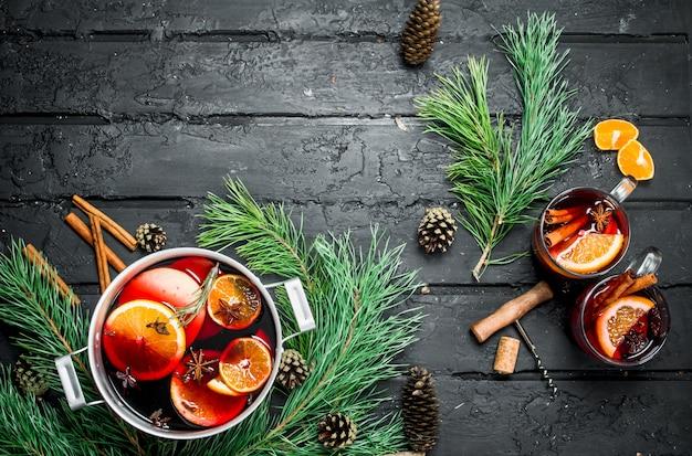 黒の素朴なテーブルにモミの枝と円錐形のホットワイン。