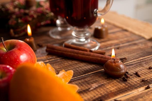 木製のテーブルにフルーツとスパイスとホットワイン