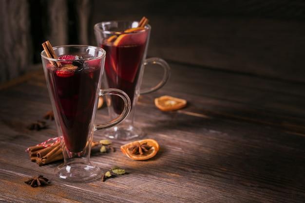 ダークウッドの背景にフルーツ、シナモンスティック、アニスとホットワイン。レシピの材料を使った冬の温かい飲み物。