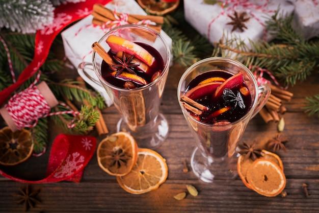 ダークウッドの背景にフルーツ、シナモンスティック、アニス、装飾品、ギフトボックスを備えたホットワイン。レシピの材料を使った冬の温かい飲み物。