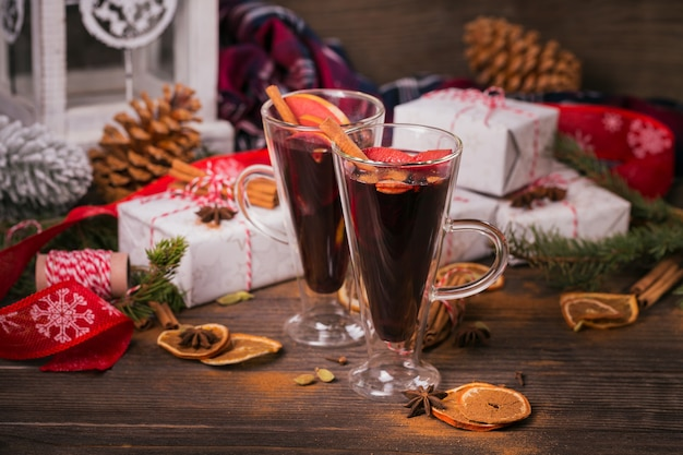 Mulled wine with fruits, cinnamon sticks, anise, decorations and gift boxes on dark wooden  background. winter warming drink with recipe ingredients.