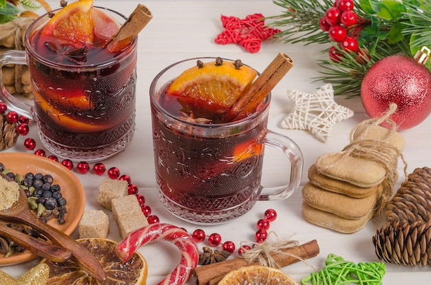 Mulled wine with orange slice, apple, cinnamon stick and spices on a white wooden background.