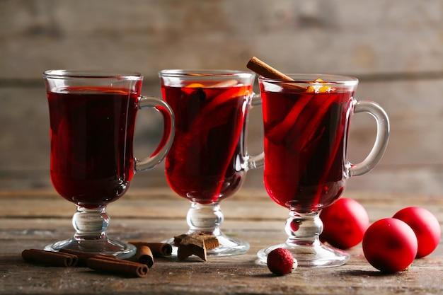 木製のテーブルに赤いクリスマスのおもちゃとホットワイン