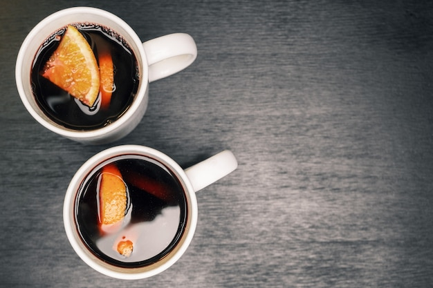 木製のテーブルの上の白いカップにオレンジのスライスとホットワイン