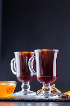 유리 머그잔에 향신료와 오렌지가 들어간 mulled 와인